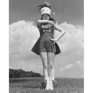 Low angle view of a drum majorette performing with a twirling baton in a field and smiling Poster Print (24 x 36)